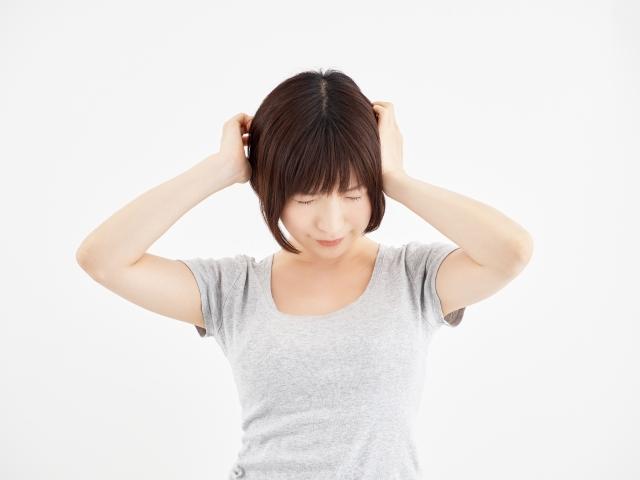 頭を抱えて悩む女性の写真