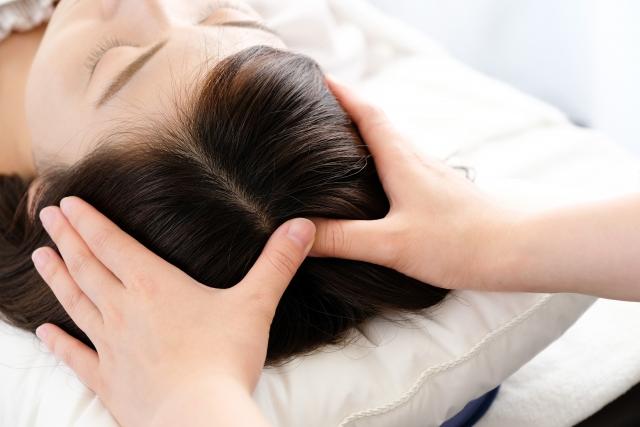 睡眠不足の解消にヘッドマッサージを受ける女性